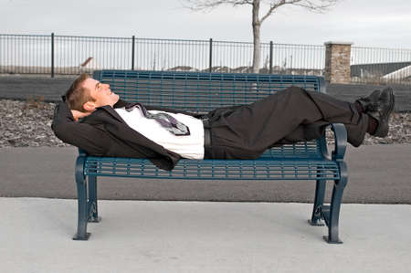 幸せな若いビジネス人が公園のベンチの上に敷設します。