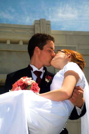 Newly married groom carrying bride and kissing her. photo