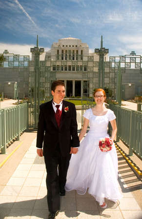 A happy young newly married couple holding hands, and walking together. Stock Photo