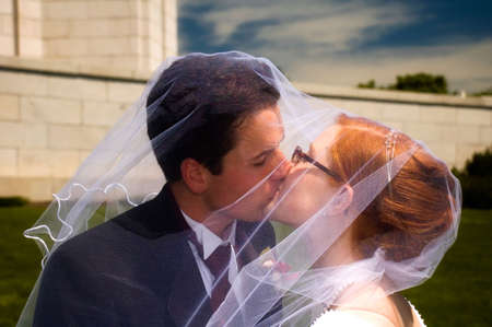 Newly weds kissing each other, under brides veil. Stock Photo