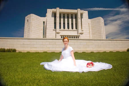 Newly married bride sitting in front of the Cardston Temple. Stock Photo