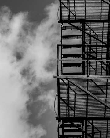 Residential staircase from a low vantage point in black and white. The metallic structure is silhouetted against the sky.