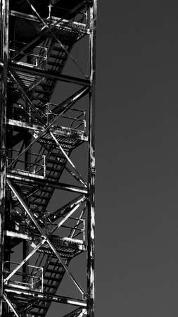 metal structure: Industrial metal structure of an old building. Heavy rust can be seen through the whole structure. An emergency staircase is visible in this black and white photo.