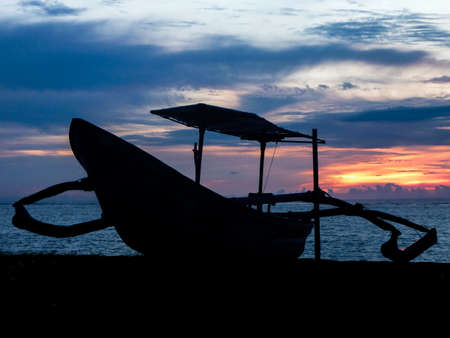 bali beach: Typical Indonesian boat on a Bali beach at sunset. Stock Photo