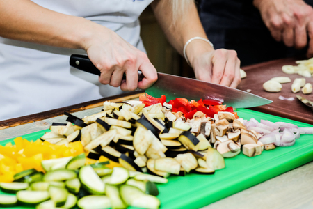 commercially: The chef in the kitchen prepares healthy food with vegetables. Stock Photo