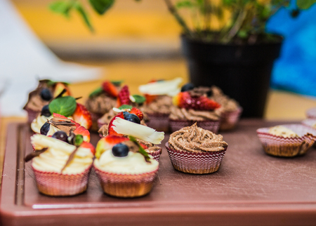 Different delicious cupcakes decorated with caramel and fresh berries.
