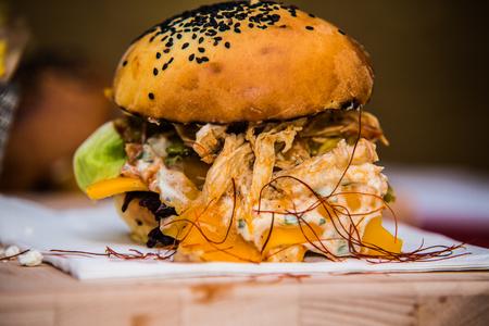 koncentrovaný: Sandwichový hamburger se šťavnatým hamburgerem a mixem zeleniny. Reklamní fotografie