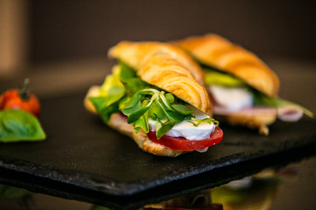 Sandwich with delicatessen cheese and fresh leaves salad.
