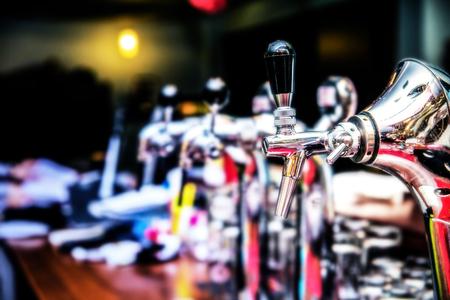 Beer faucets in a bar. Metallic beer taps. Beer tap at restaurant. Foto de archivo
