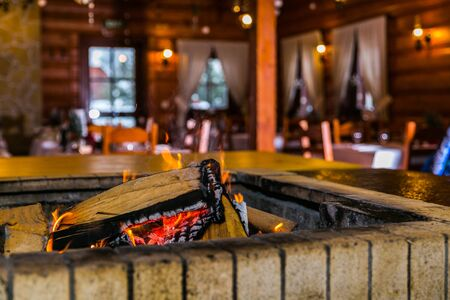 Cosy style restaurant with a stove wood fire burning in fireplace. Hot embers in a bonfire. Closeup