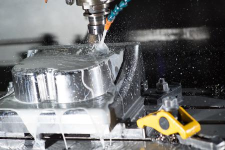 stop motion di centro di lavoro CNC fresatura di una parte di muffe durante l'utilizzo di liquido di raffreddamento. Archivio Fotografico