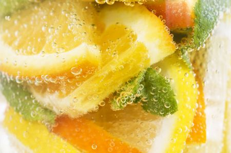 Close-up of citrus fruiits and mint leaves in mineral water photo