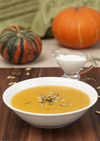 Bowl with pumpkin soup and pumpkins