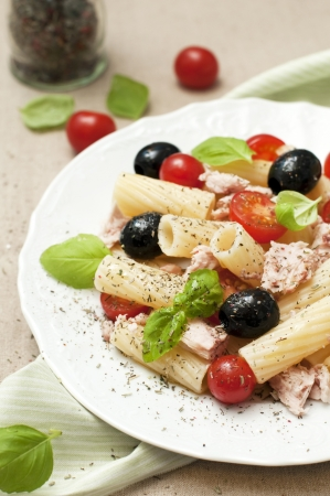 Fresh salad with pasta, cherry tomatoes, black olives, tuna and basil photo