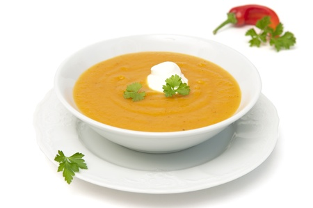 Bowl with pumpkin soup and chili pepper photo