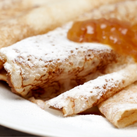 close up of crepes with powdered sugar and jam, square image