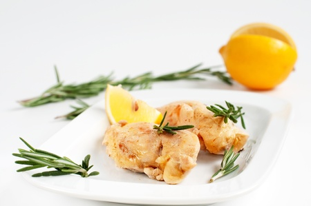 Chicken breast fillet with fresh lemon and rosemary on white plate Stock Photo