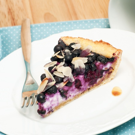 Slice of blueberry cheesecake with almond, square image