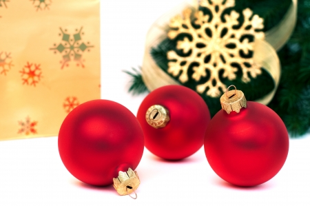 Three red christmas balls, gift bag and fir with snowflake, isolated on white