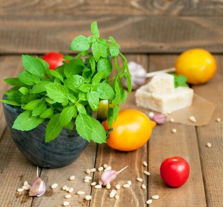 Fresh basil, tomatoes, garlic and parmesan on wooden table, horizontal