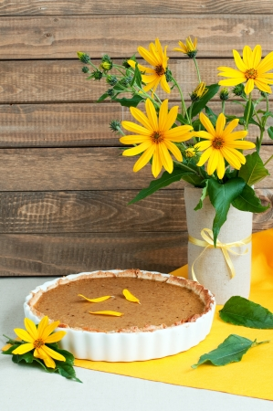 Whole home baked pumpkin pie in ceramic dish and daisy, rustic still life, vertical