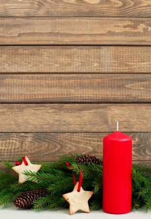 Christmas fir with star cookie and cones next to candle on table with space for text, vertical photo