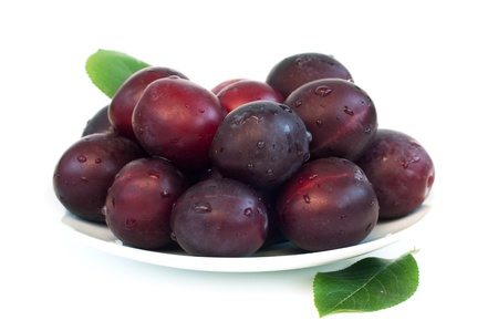 Fresh plums on plate over white background Stock Photo