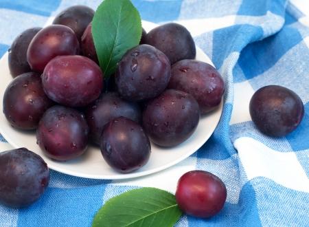 Fresh plums on plate selective focus, horizontal