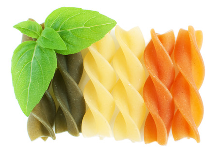 Close up of colorful rotini pasta with basil isolated on white, macro shot photo