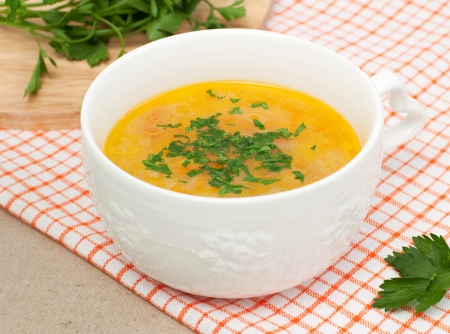 Close up of bowl with vegetables soup and fresh parsley, selective focus, horizontal Stock Photo