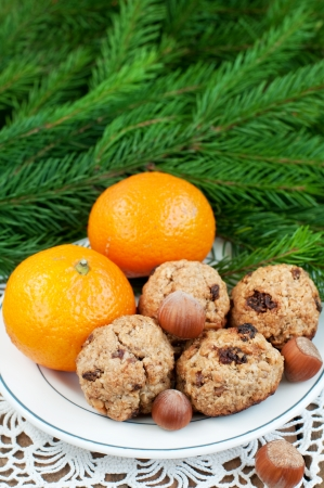 Plate with oatmeal cookies, tangerines and nuts, christmas fir in background, vertical