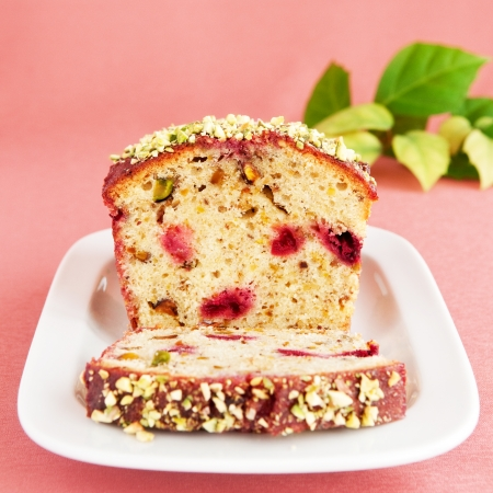 Close up of pistachio cake with cherry over pink background, square image Stock Photo
