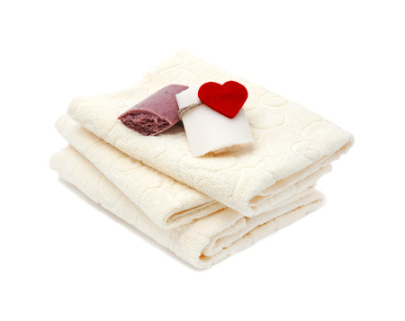 Three bath towels and handmade soap decorated with heart isolated on white background