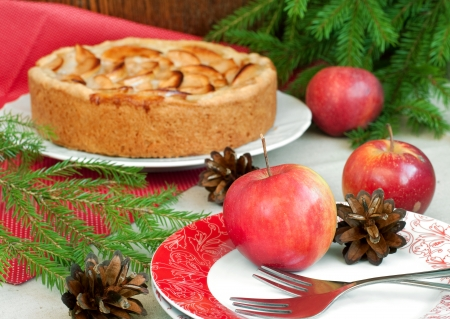 Table setting with apple pie, fresh apples and christmas fir, horizontal