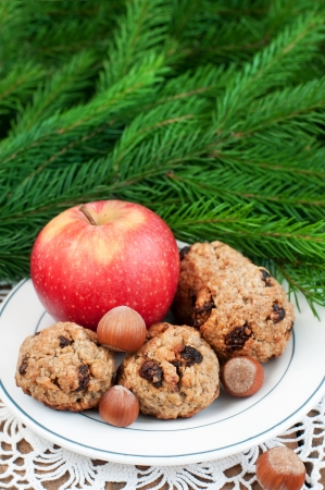 Close up of oatmeal cookies, apples and nuts on plate, christmas fir in background, vertical Stock Photo