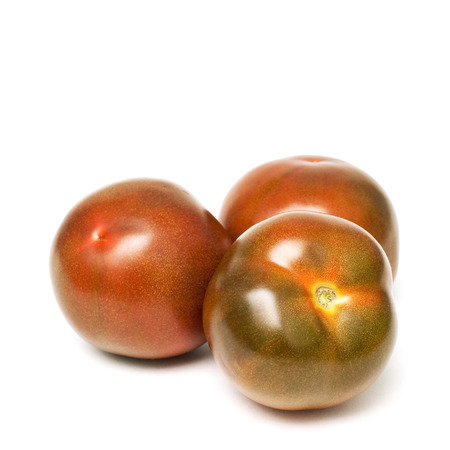 Three kumato tomatoes isolated on white background
