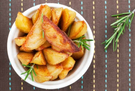 Top view of roasted potatoes with rosemary, selective focus, horizontal Stock Photo