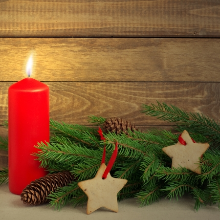 Christmas card with red candle and holiday fir on table, rustic style photo