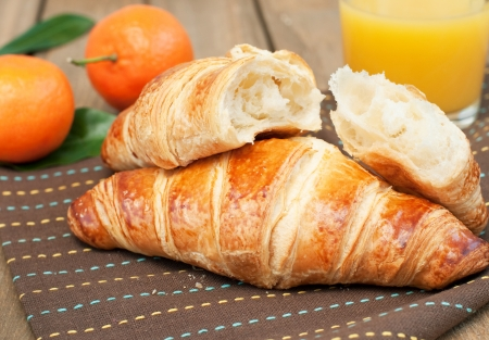 Close up of two fresh tasty croissant and orange juice, horizontal Stock Photo