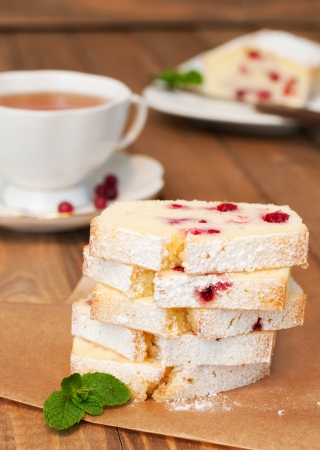 Partly slices semolina cranberry cake and cup of tea on wooden table photo