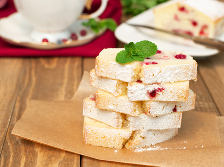 Partly slices semolina cranberry cake and cup of tea on wooden table, horizontal photo