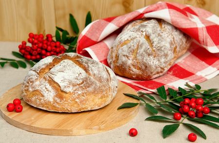 Two loaf of bread on table and rowan, horizontal Stock Photo