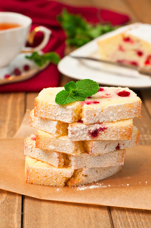 Slices of fresh semilona cake with a cake and cup of tea in the background, vertical Stock Photo
