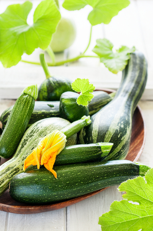 Fresh organic zucchini on the white wooden table, vertical, selective focus Stock Photo