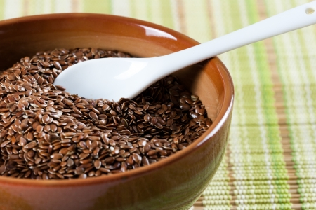 Brown flax seeds in brown green bowl with a white ceramic spoon  photo