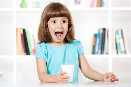 Little girl with glass of milk making a face Stock Photo - 15690072