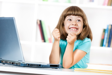 Cute little girl is very excited about using her laptop Stock Photo