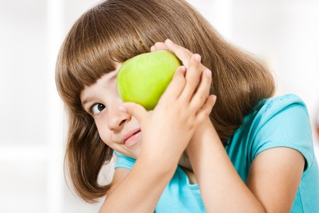 Beautiful little girl holding apple in her hands photo