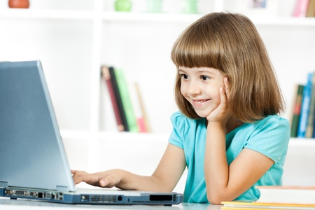 cute little girls: Cute little girl smiling and looking at laptop  Stock Photo