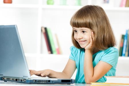 ni�as peque�as: Ni�a linda que sonr�e y que mira en la computadora port�til Foto de archivo